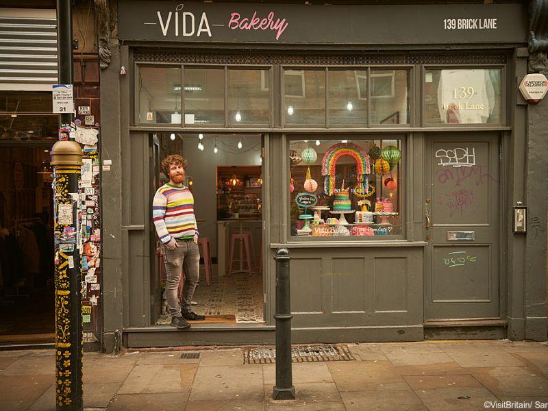 Young man standing in the doorway of Vida Bakery, Brick Lane, Shoreditch, London, UK