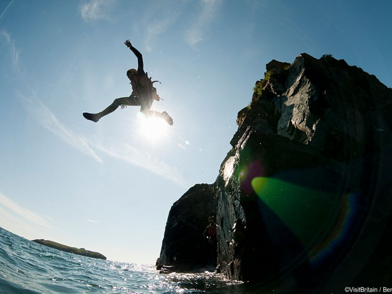 Coasteering, a person jumping into the sea at Mullion Cove, Cornwall, England.