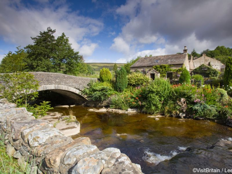 A riverside cottage in Dentdale, Yorkshire Dales National Park. The river Dee and a historic stone bridge