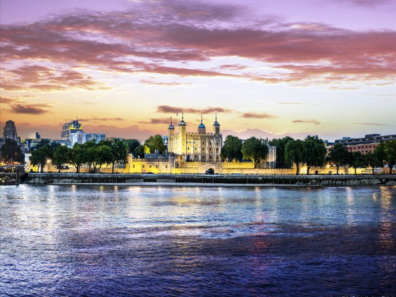 The Tower of London at twilight viewed from across the River Thames, London, England.