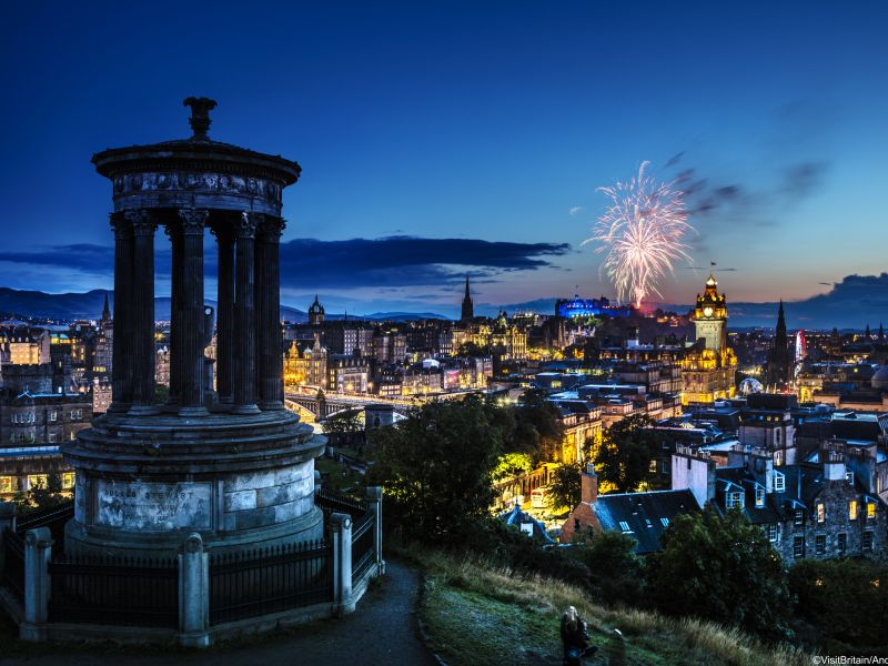 View from Calton Hill over the city of Edinburgh and the historic buildings at night, during the annual Military Tattoo. Fireworks in the night sky. Lothian, Scotland