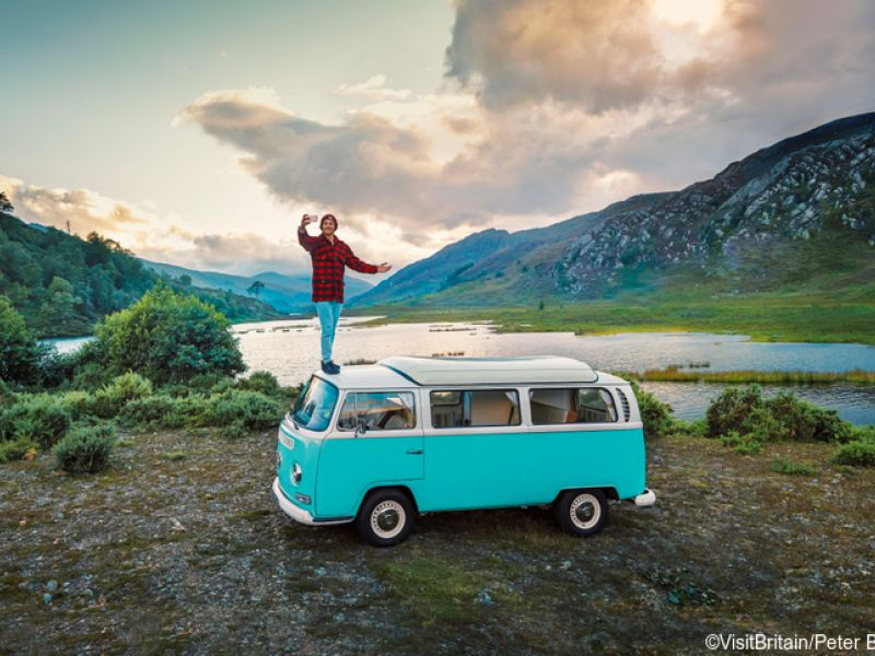 Man standing on camper van taking a selfie on the shore of Loch Ness in the Scottish Highlands.