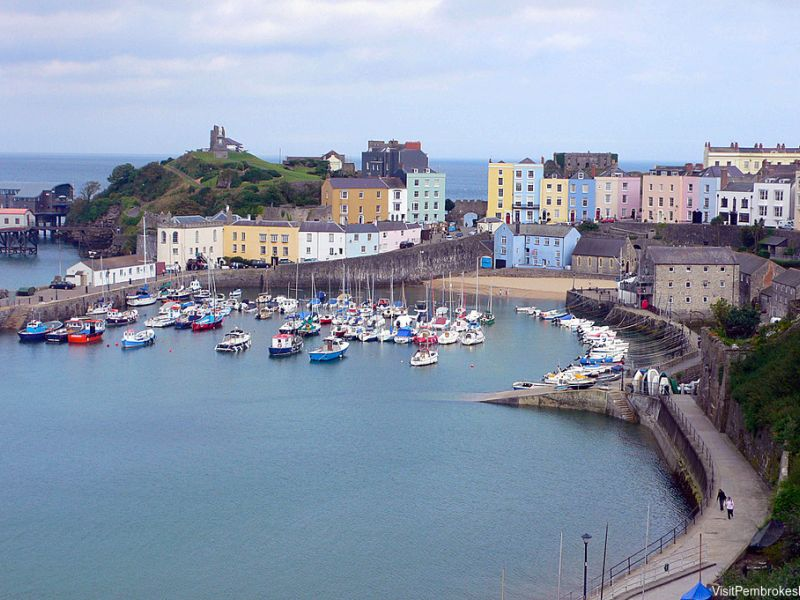Tenby harbour, Pembrokeshire, Wales. Pastel coloured houses surround the harbour. Fishing boats moored.