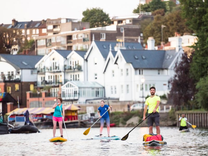 Group of people paddle boarding on the River Thames, Richmond, London, England.