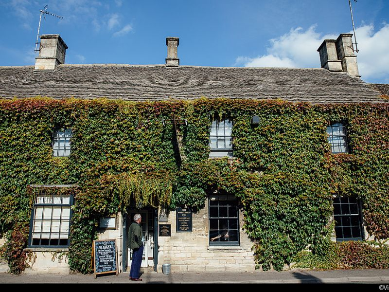 Man standing outside The Wheatsheaf Inn, Cotswolds, England.