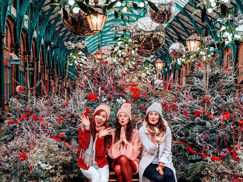 Three girls sitting by Christmas Trees at Covent Garden Market, London, England