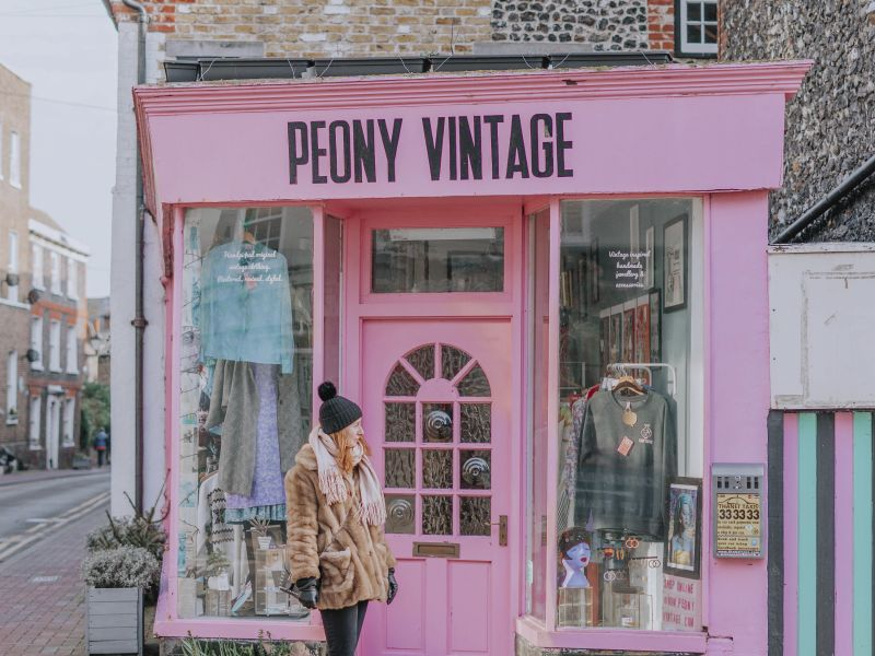Young woman walking in front of Peony Vintage clothing shop, Margate, Kent, England.