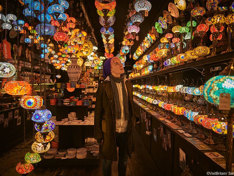 One young woman standing in a lighting shop in Camden Market, Camden, London, UK