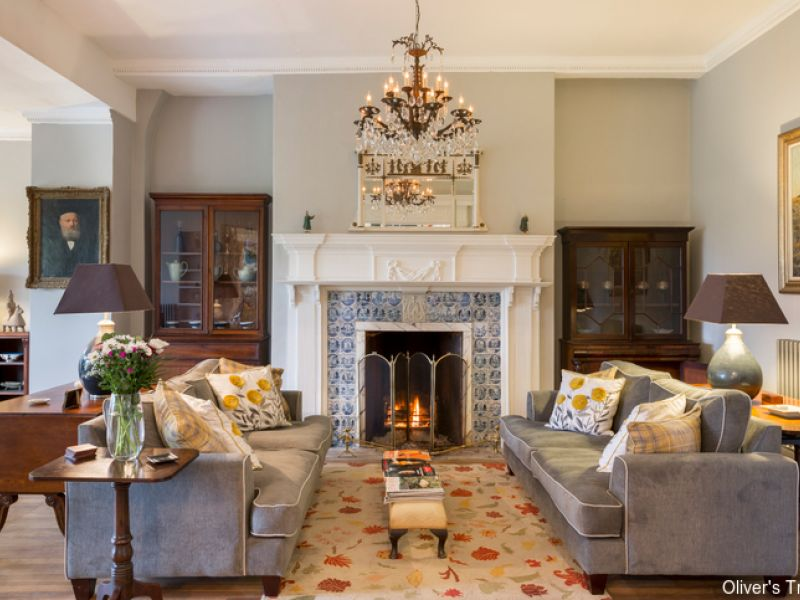 Living room at Colleton Hall, North Devon. Cosy living space with sofas, artwork and antique furniture.