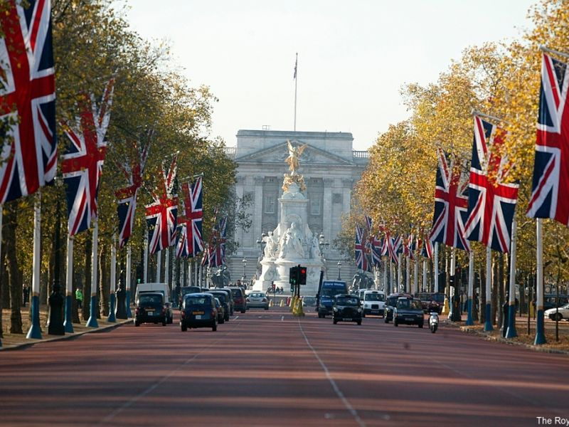 The Mall heading towards Buckingham Palace, London. Lined with trees and Union Jack flags.