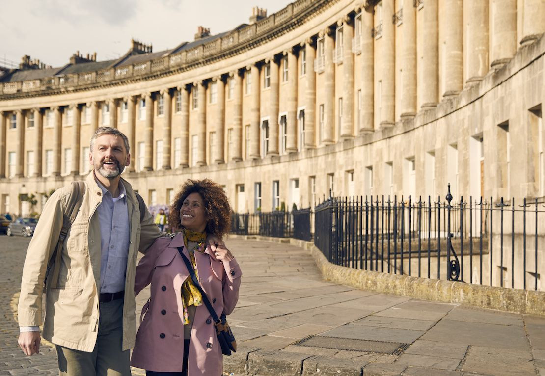 Couple looking happy in front of the Royal Crescent in Bath