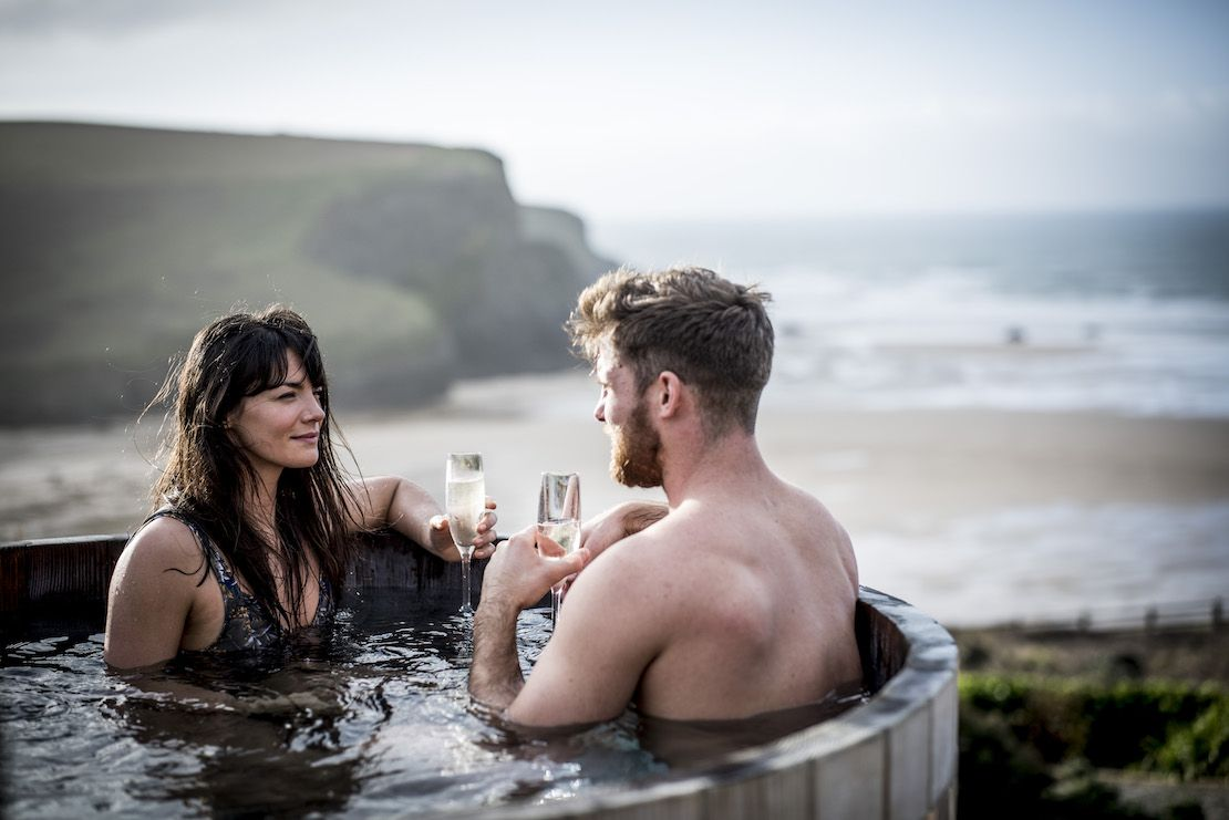 Couple relaxing in a hot tub by the sea in Cornwall