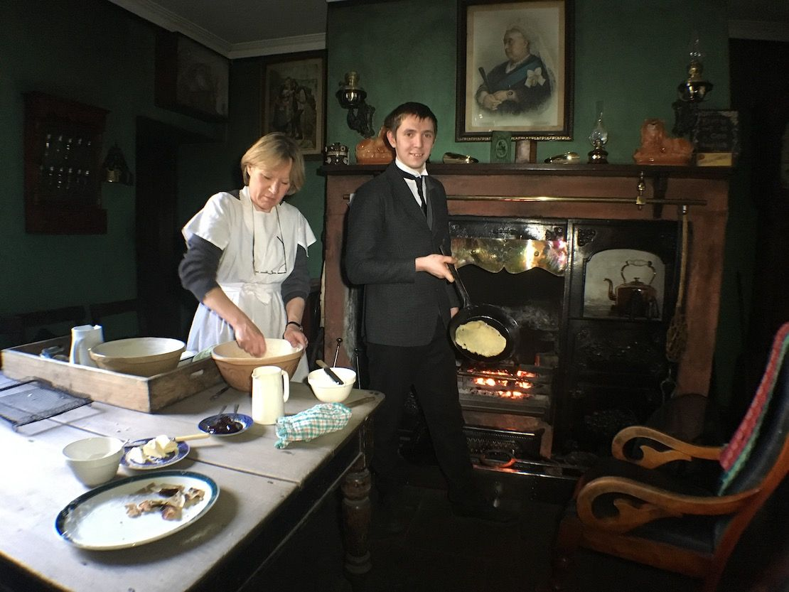 Woman making pancakes in historical costume at Beamish Museum.