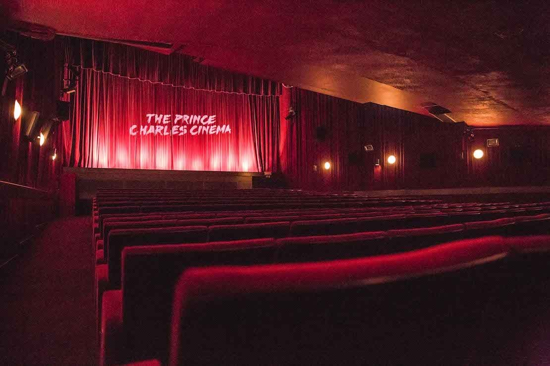 The screen and red seats inside The Prince Charles Cinema, London