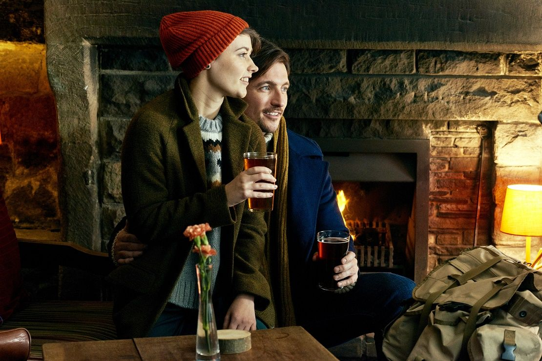 Couple enjoying a pint in front of the fire at a traditional British pub
