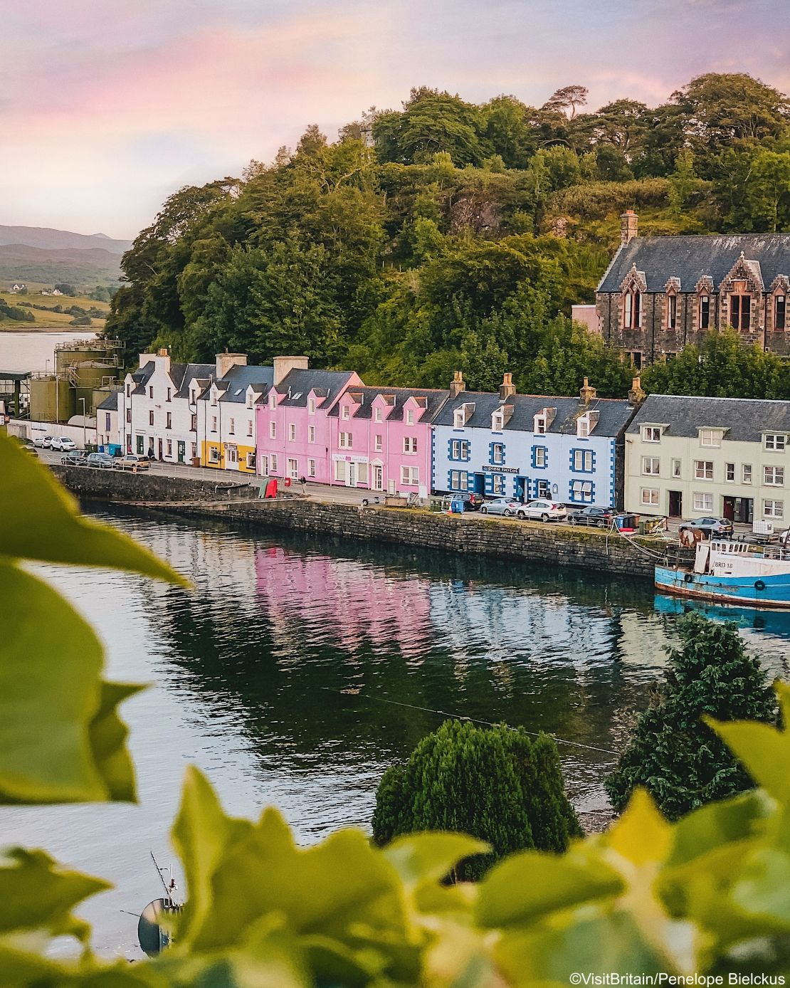 Colourful painted terraced painted houses along the harbour wall with reflections in water, Portree, Isle of Skye, Scotland.