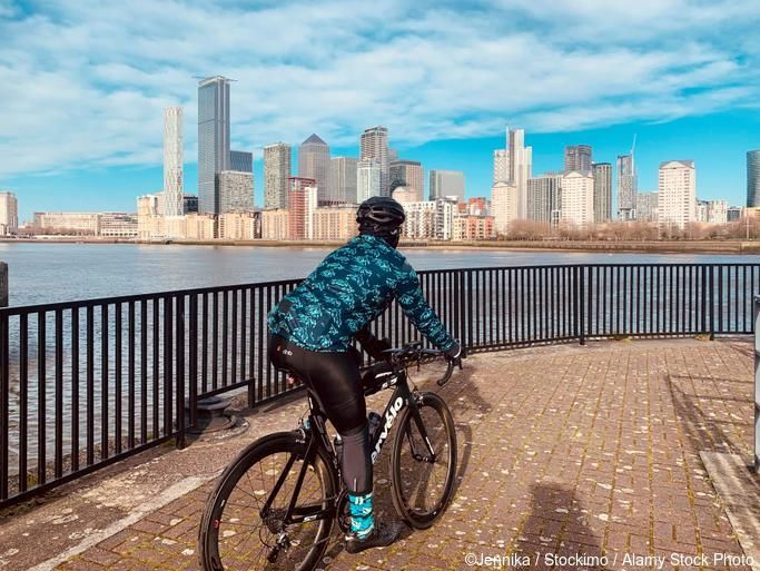 Cycling by the river Thames on a sunny day in London with Canary Wharf in the background
