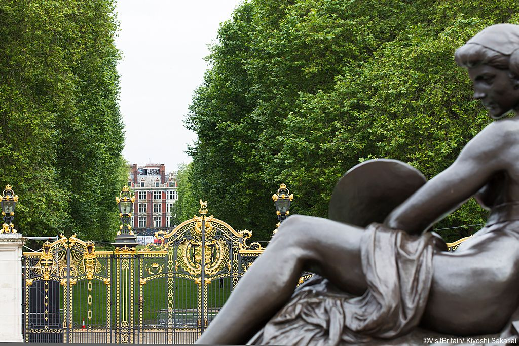 A view from Green Park, from the Canada Gates, wrought iron gates, an avenue of mature trees and a view to a historic building. A bronze statue at the base of the Victoria statue in the Mall.