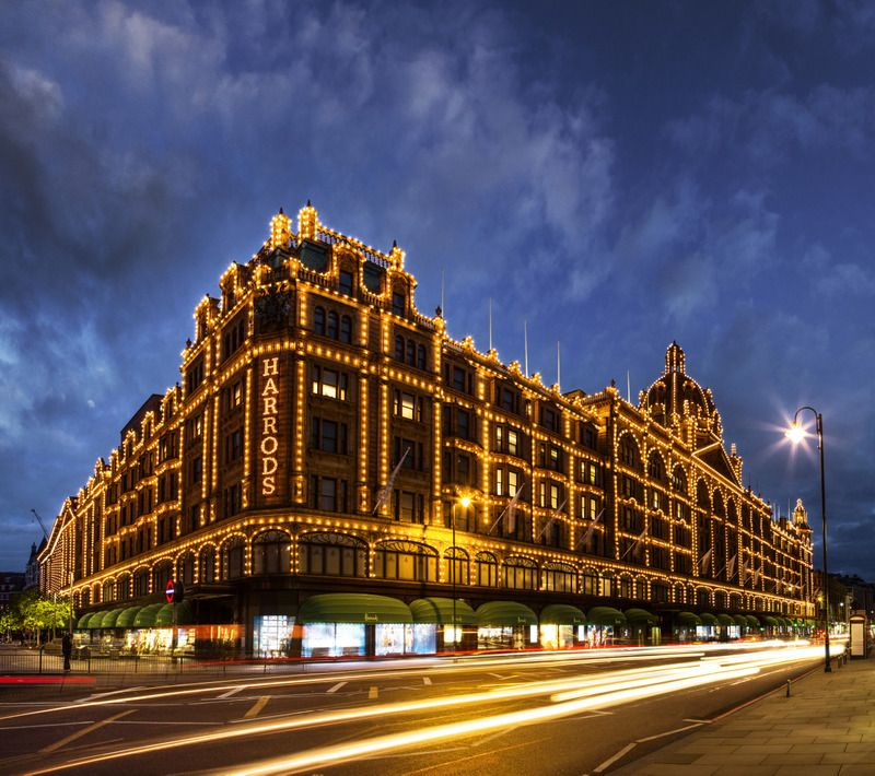 Harrods department store in Knightsbridge is lit up at night with a huge array of lights, silhouetting the building features
