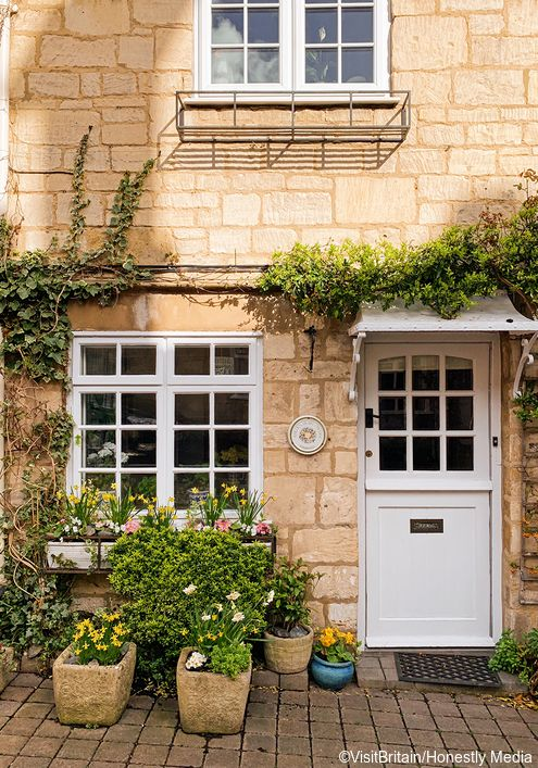 charming facade of a stone house in Painswick, Cotswolds, England