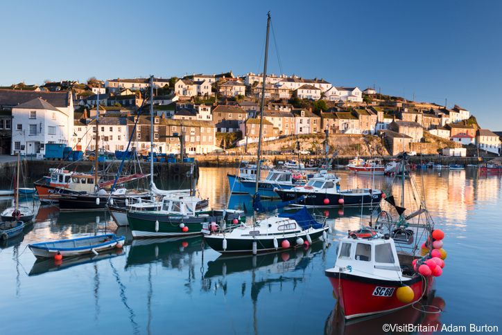 A historic fishing harbour with a curving sheltering harbour wall. Flat calm sea. Boats moored. Houses on the hillside. South Cornish coast.