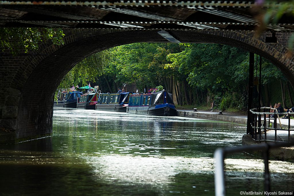 An iron bridge over the Regents Canal in Camden, London. A group of traditional narrowboats, houseboats moored.