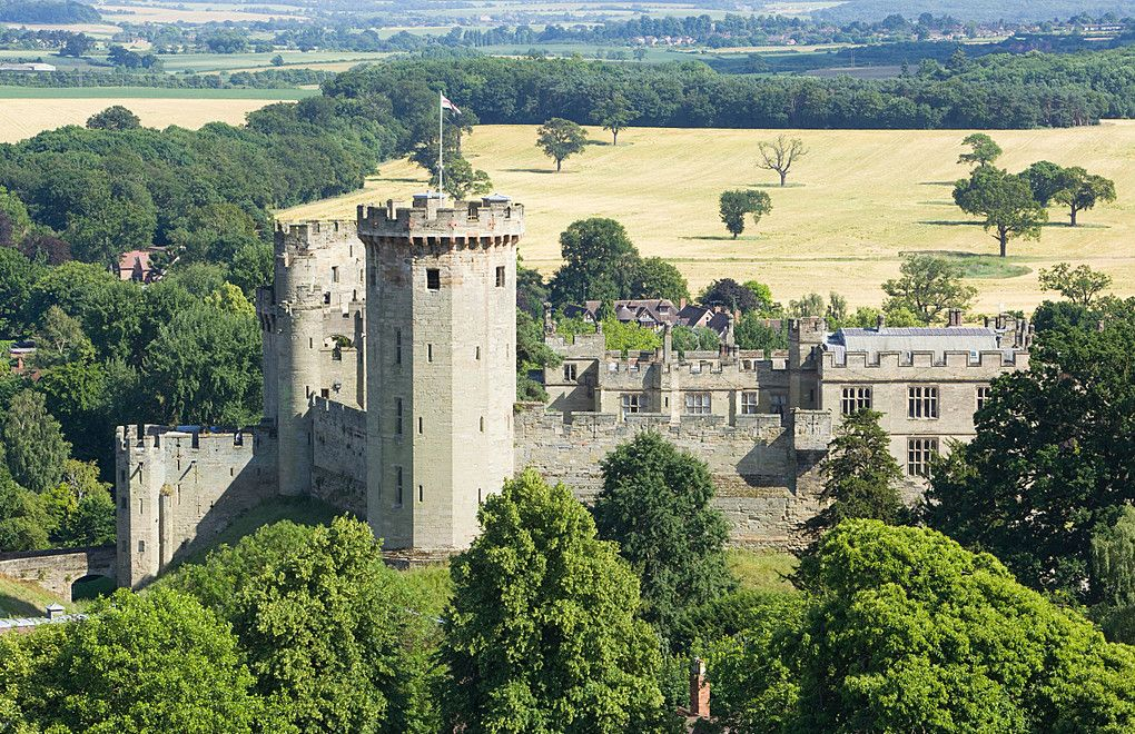 Warwick Castle from St. Mary's Church Tower, Warwick, Warwickshire, UK. Grand and imposing castle in view. Green landscape and open space. Countryside and rural scene.