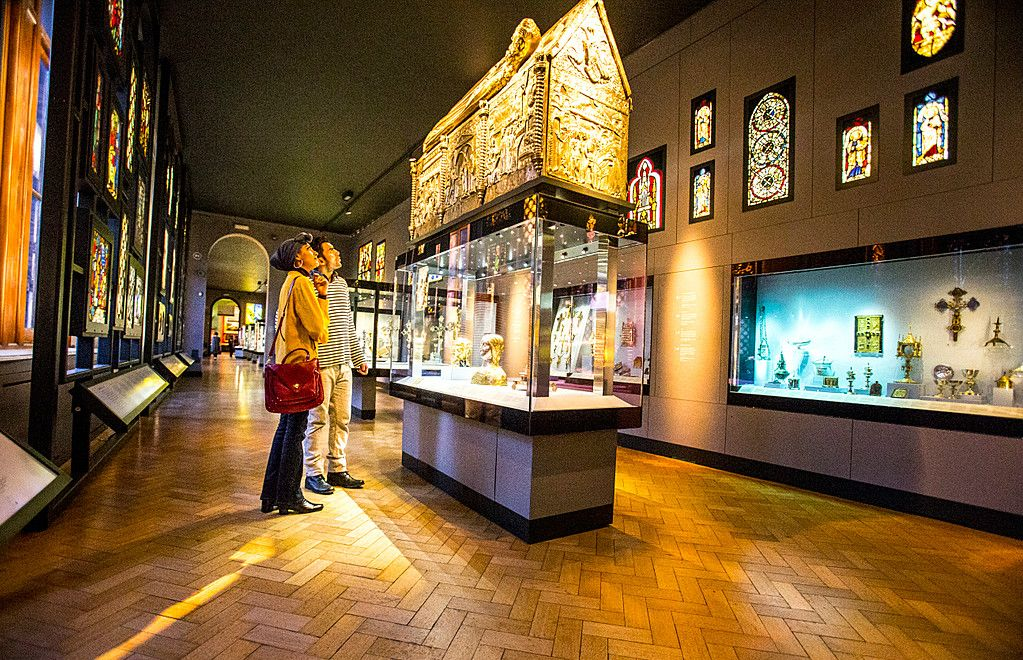 Arabic family at the V&A Museum, London. Parents, woman and man, looking at artefacts and busts in display case. Stained glass windows.