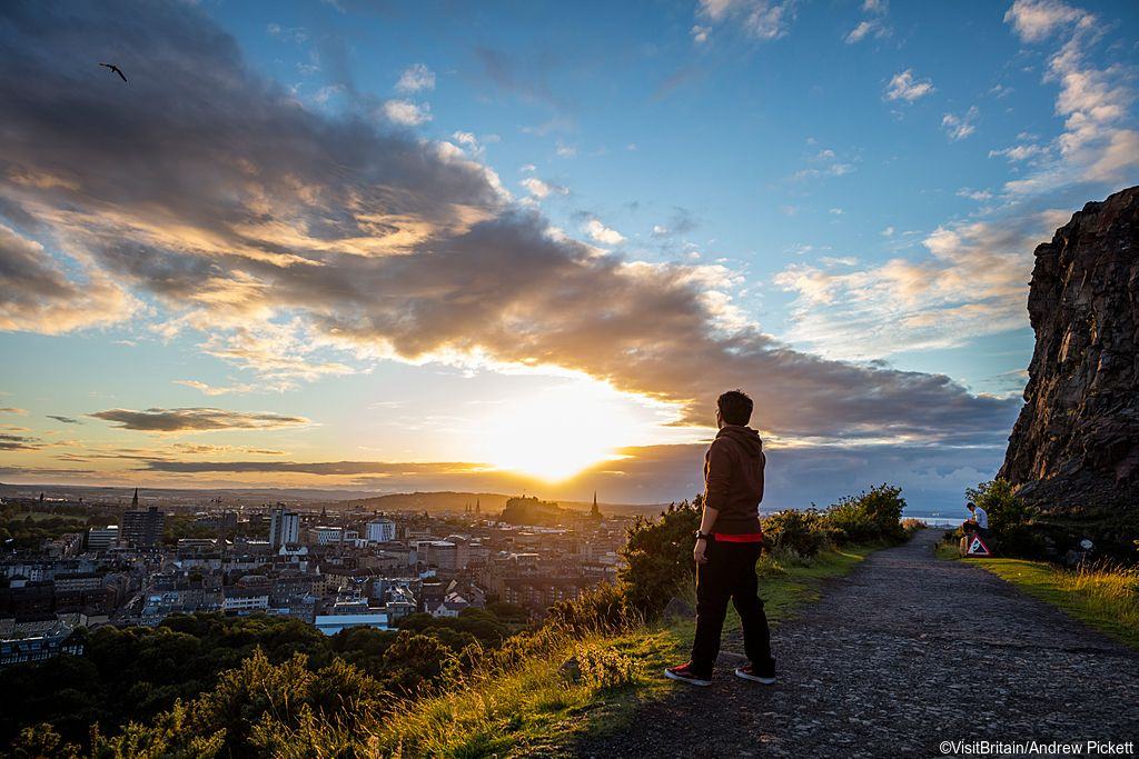 View from Salisbury Crags at sunset. Young man standing on a footpath along the cliffs at the top of a subsidiary spur of Arthur's Seat which rise on the west of Holyrood Park, overlooking Edinburgh.
