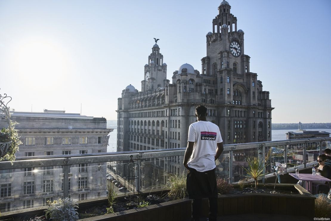 Young man standing on restaurant roof terrace near Royal Liver Building, Liverpool, Merseyside, UK.