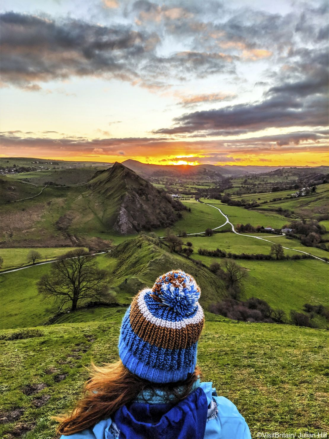 A woman sitting at the top of Chrome Hill, Derbyshire, enjoying the view and sunset.