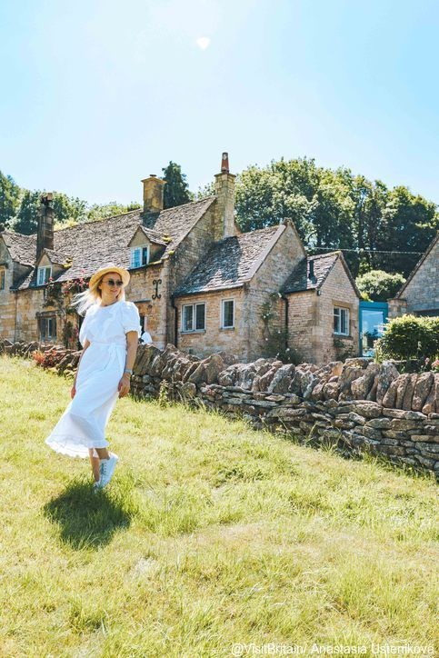 A woman standing in a field wearing a white dress in Snowshill, Gloucestershire, England. Credit to VisitBritain/ Anastasia Ustenikova