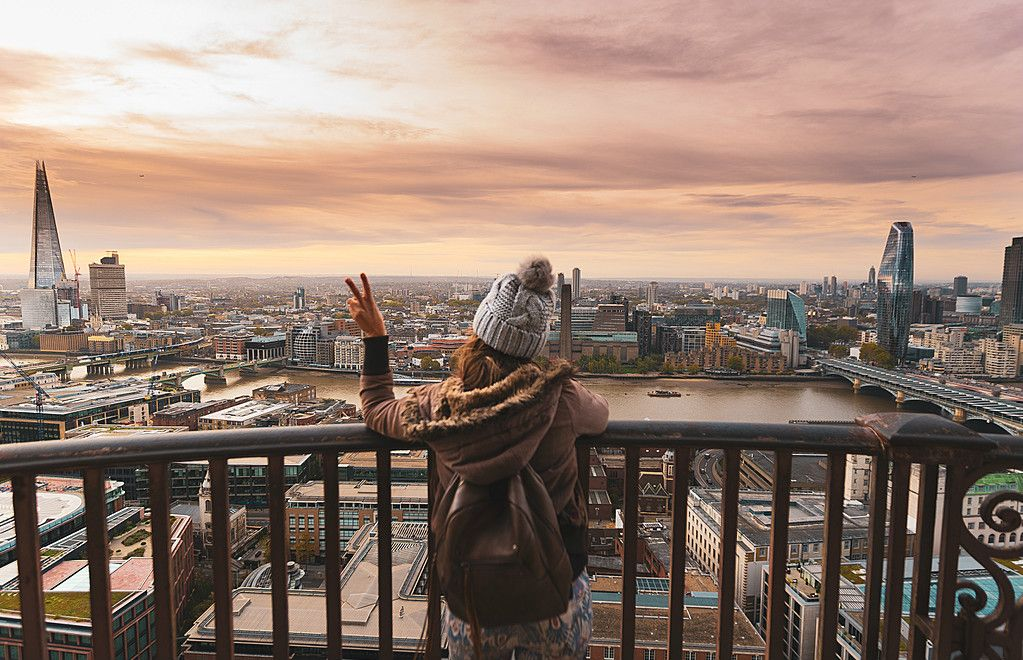Woman at the top of St Paul's dome at sunrise with city view