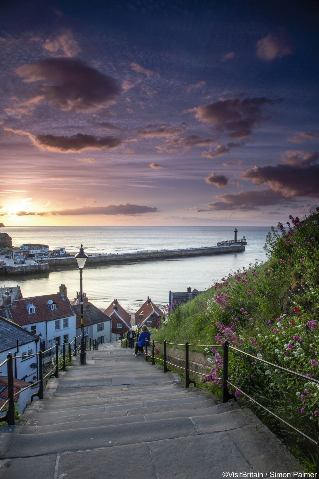 Two people on the steps of a hillside looking towards the pier at Whitby, North Yorkshire, England