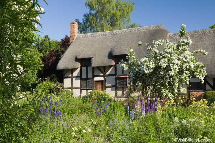 Anne Hathaway's Cottage and Gardens. Exterior view of a thatched cottage and gardens where Anne Hathaway, wife of William Shakespeare, lived as child. Farmhouse with thatched roof. Pathway going through garden. Managed by Shakespeare Birthplace Trust. Tra