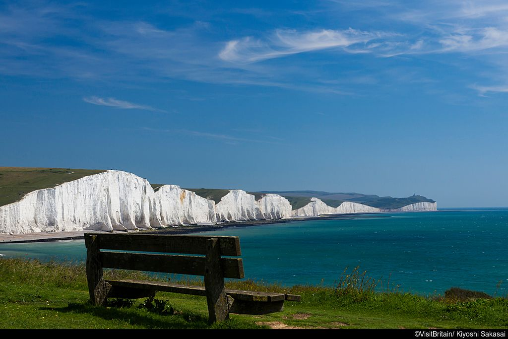 Viewpoint and bench seat on the cliffs at Hope Gape, looking along the coastline of the Seven Sisters white chalk cliffs on the English channel.