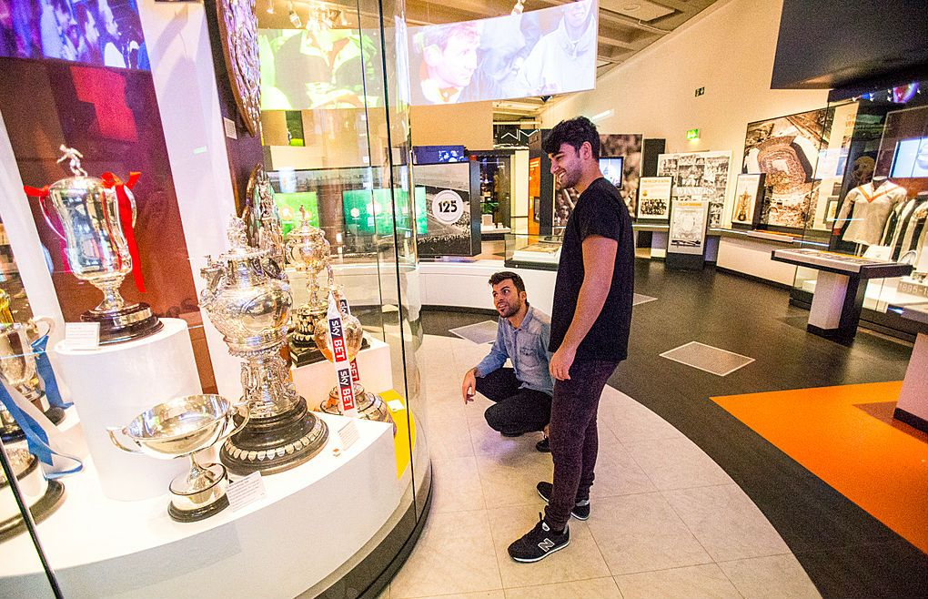 The National Football Museum. An Arabic family, a father and son visiting the museum. Using interactive exhibits about the game of soccer and its history.