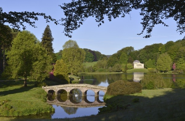 Classic English landscape with lake, bridge and temple folly, framed by the silhouettes and shadows of surrounding trees Stourhead, Wiltshire, UK© iStock/ oversnap