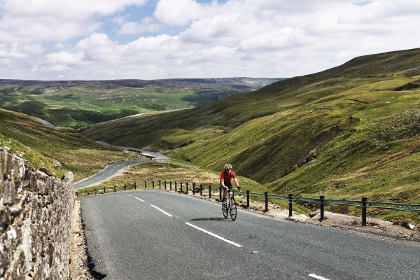 The English start point in Yorkshire for the 2014 Tour De France. Buttertubs pass, and the view over the dales landscape. Cyclist on the road.