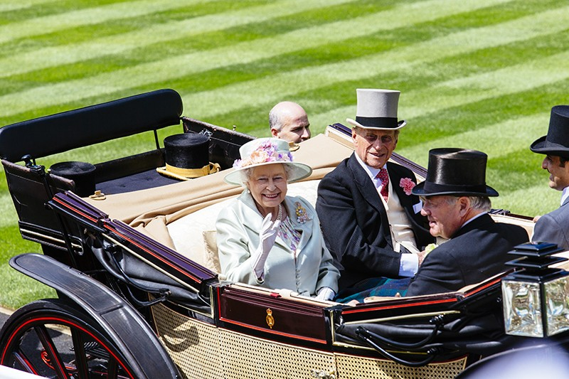 Queen Elizabeth II and Prince Philip sitting in a horse-drawn carriage