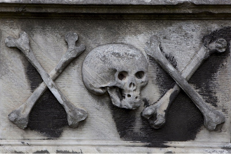 Stone skull with two cross bones on either side on a tomb at Greyfriars Kirkyard, Edinburgh, Scotland.
