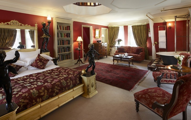 The red and gold Rook's Nest room at The Rookery Hotel London. Gold faux bamboo framed bed has two black cherubs at its feet, and red rose bedspread. Vintage Victorian bath in top right corner of image.