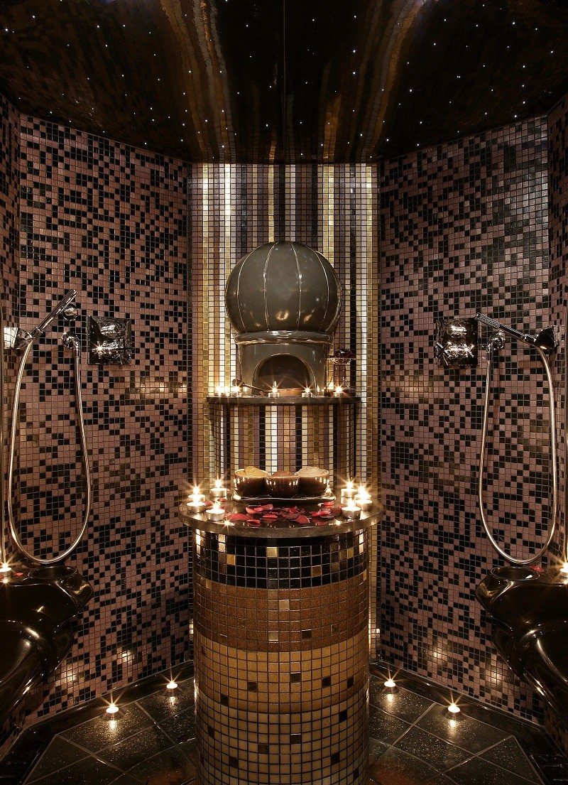 Moroccan style spa temple at Spa Intercontinental, Park Lane. Pink, gold and dark brown mosaic tiles decorate walls, tea lights and rose petals decorate plinth and there are tea lights on the floor too.