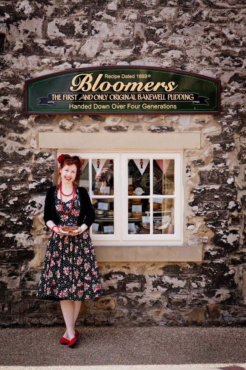 British food fan in vintage dress outside Bloomers Bakewell pudding shop, holding a Bakewell Pudding.