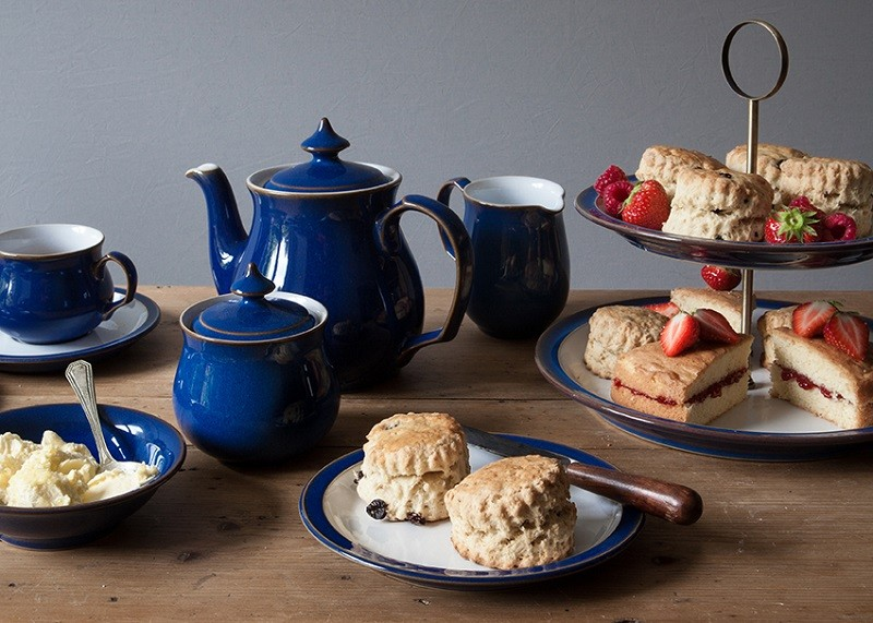 English afternoon tea laid out on a wooden table, with blue teapot, cup and jugs, with tiered plate of scones, cakes, strawberries and cream.
