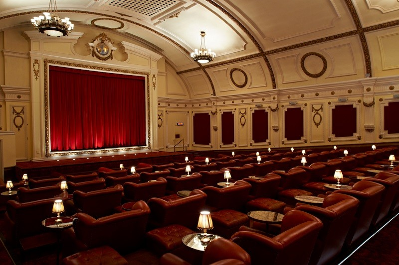 Inside Electric Cinema Portobello, with red armchairs, side tables and lamps, and a red velvet curtain across the main screen.