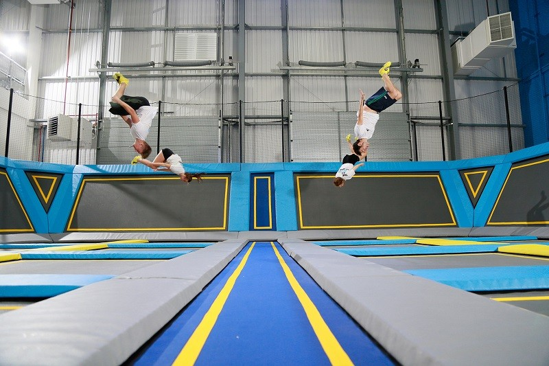 Four people bouncing upside down on a trampoline at Oxygen Freejumping in Acton, London.