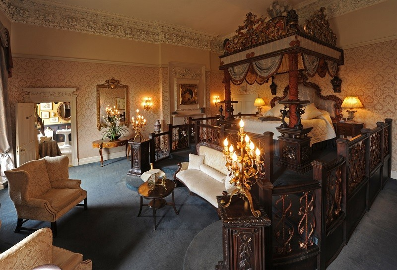 Lady Craven Bedchamber at Coombe Abbey, with elaborate golden bed on a plinth and candelabras in the foreground.